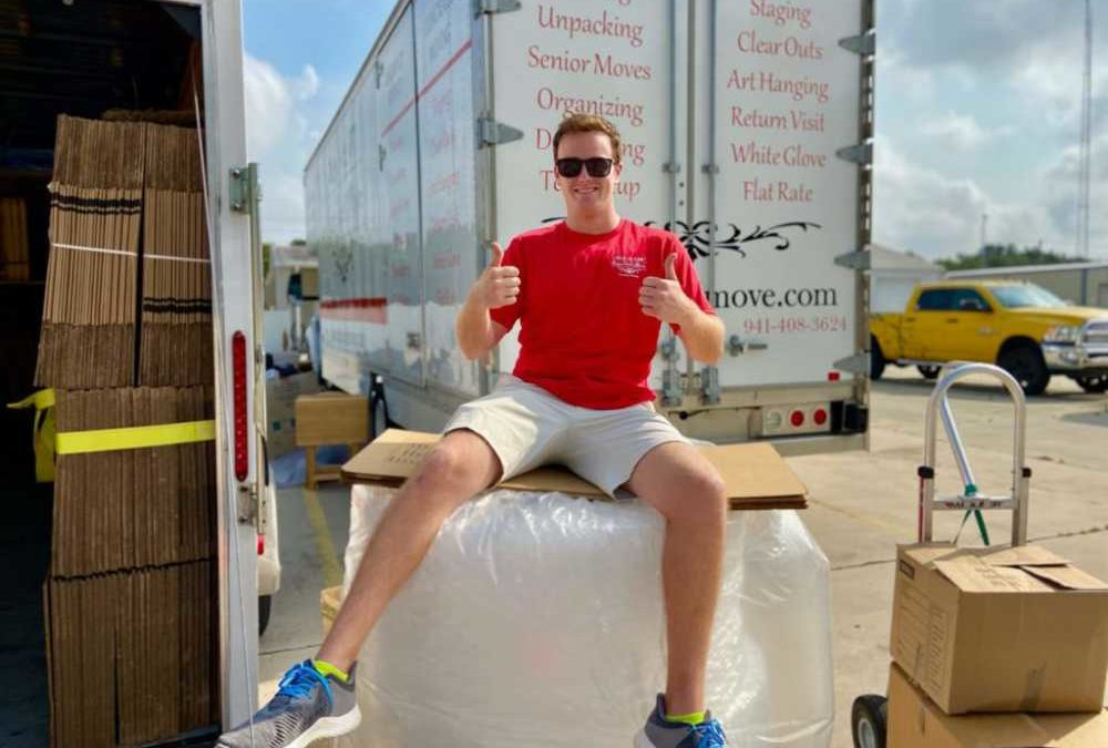 local business owner sitting on top of moving boxes with thumbs up